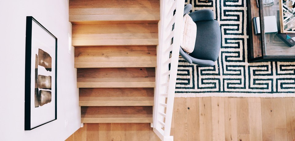 birds-eye view of hardwood stairs with carpet